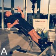 """Der Core-Soldier ist eine kreative Variante für dein Bauch-Training im Studio. Hierfür haben wir die gute alte Hyperextension-Bank einfach umfunktioniert. Funktioneller und effektiver kannst du mit keinem anderen """"klassischen"""" Studiogerät deine Rumpfmuskulatur trainieren. Bei dieser Übung wird die Bauchmuskulatur vor allem in der Funktion der AntiÜberstreckung beansprucht."""